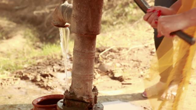 Woman filling earthen pot through a hand pump, Haryana, India