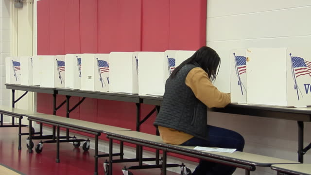 ms, woman filling her voting ballot at voting booth, toledo, ohio, usa - voting booth stock videos & royalty-free footage
