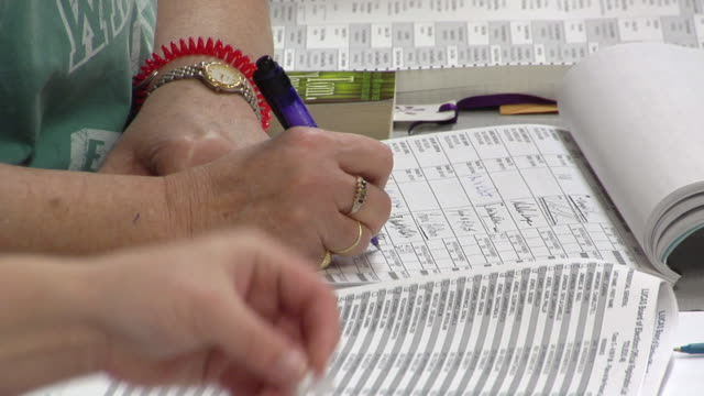 cu, woman filling in registration paperwork at polling place, toledo, ohio, usa - demokratie stock-videos und b-roll-filmmaterial