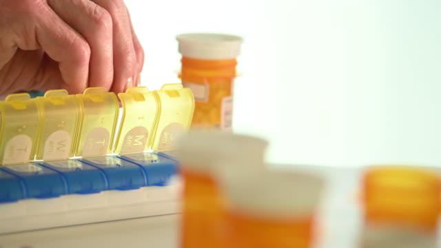 Woman Filling Pill Box At Table