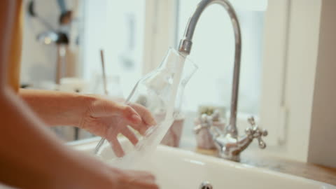 woman filling tap water into glass bottle at home - waschbecken stock-videos und b-roll-filmmaterial