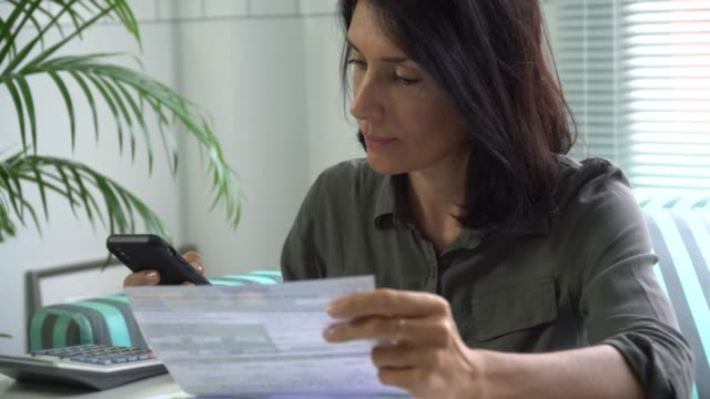 woman filling tax form paying bill on smart phone, mobile payment - tax form stock videos & royalty-free footage