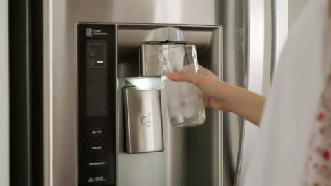 vídeos y material grabado en eventos de stock de mujer llenando taza de agua de la nevera del hogar - cocina electrodomésticos