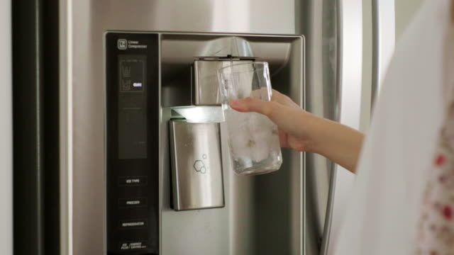 woman filling water cup from home refrigerator - refrigerator stock videos & royalty-free footage