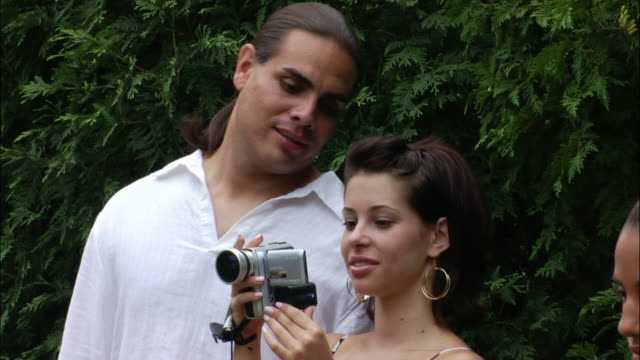 Woman filming home movies with digital camcorder at birthday party with man looking at viewfinder over her shoulder / New Jersey