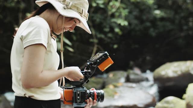 vidéos et rushes de femme cinéaste filmée en document - caméraman