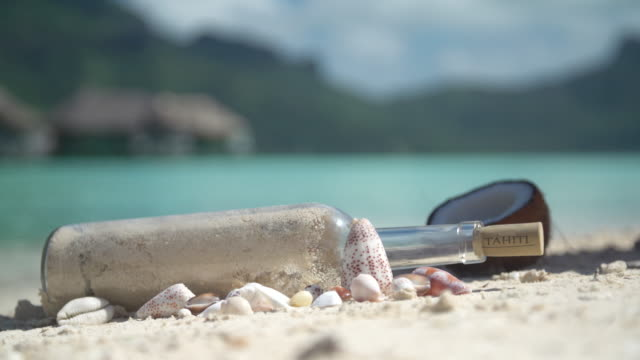 a woman finding a message in a bottle in tropical islands in french polynesia. - messaggio video stock e b–roll