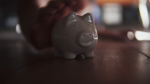 woman finding lost piggy bank under sofa. - currency symbol stock videos & royalty-free footage