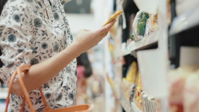 woman finding product inside supermarket - borsa della spesa video stock e b–roll