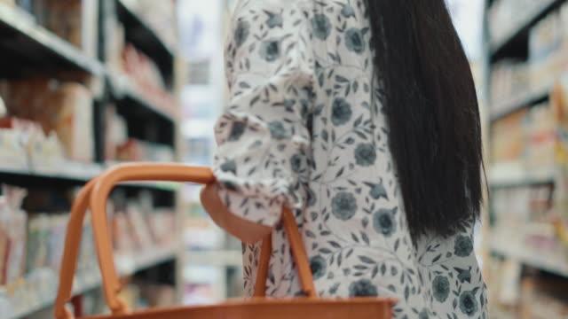 Kvinna att hitta produkten inuti stormarknad