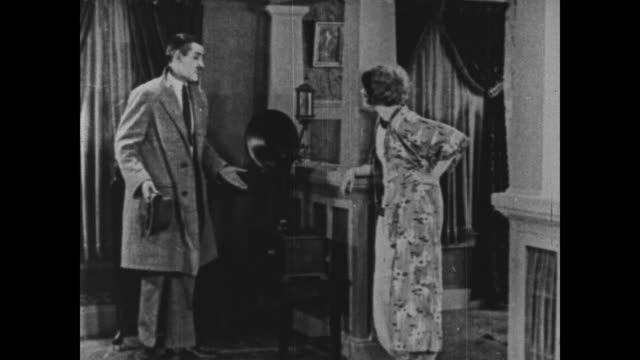 1925 woman finds man hiding in the dark, turns on light and pulls him from the room by his ear - stealth stock videos and b-roll footage