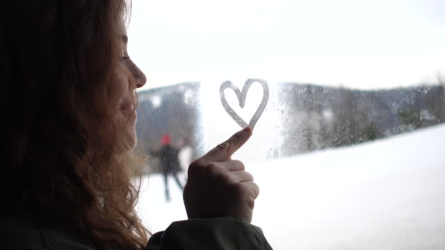Woman finger painting a heart on foggy window