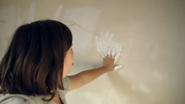 woman finger painting with white paint on wall, slow motion - finger painting stock videos and b-roll footage