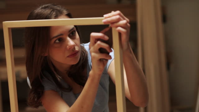 Woman finishing picture frame in workshop
