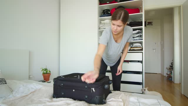 woman finishing with unpacking luggage, putting the suitcase on the floor - luggage stock videos & royalty-free footage