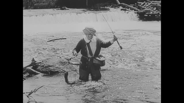 vídeos de stock, filmes e b-roll de 1923 woman (phyllis haver) fishes in rushing river - 1923