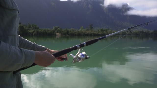 woman fishing at a lake in the mountains - angeln stock-videos und b-roll-filmmaterial