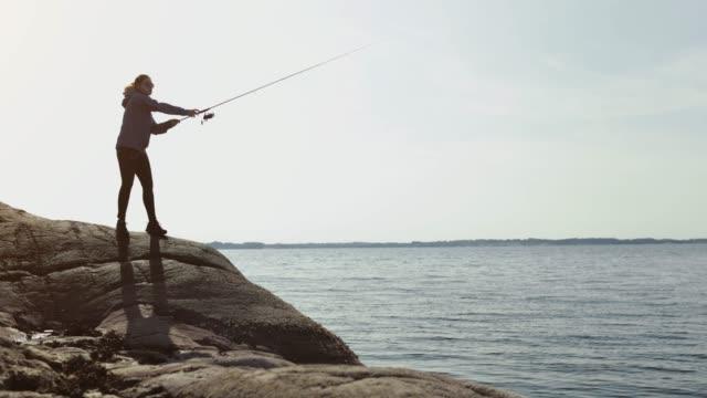 vidéos et rushes de femme pêchant avec une tige d'une tache de roche - lancer la ligne de canne à pêche