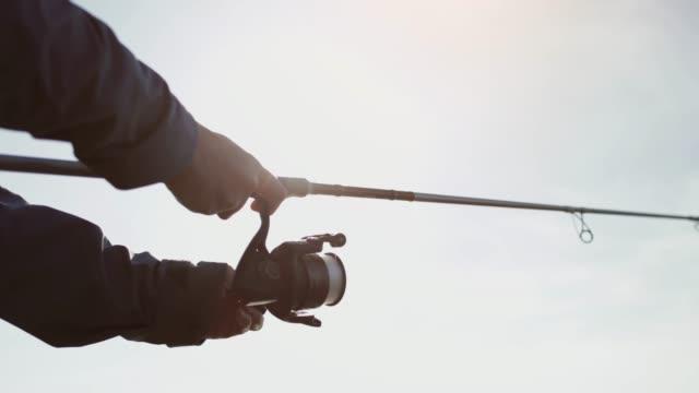 Vrouw vissen met een staaf van een rots ter plaatse