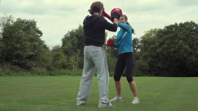 MS Woman fitness boxing with personal trainer in park, London, England