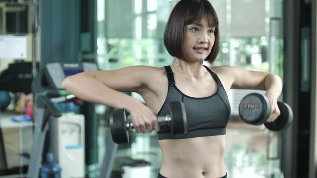 woman fitness woman working out with dumbbells at a gym - flexing muscles stock videos and b-roll footage