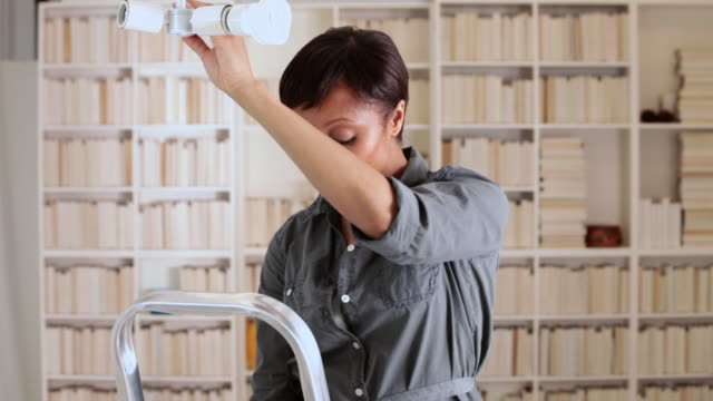 woman fitting a lightbulb - changing lightbulb stock videos & royalty-free footage