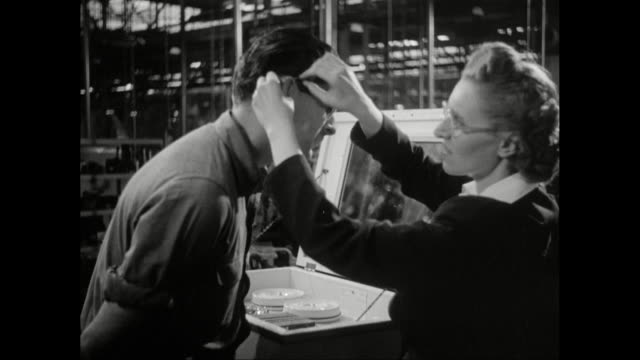 ms woman fitting man with safety glasses / united states - occhiali da vista video stock e b–roll