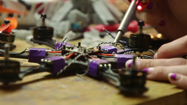 woman fixes and prepares self-made drone, montage - electronics industry stock videos & royalty-free footage