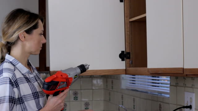 DIY woman fixing cabinet door