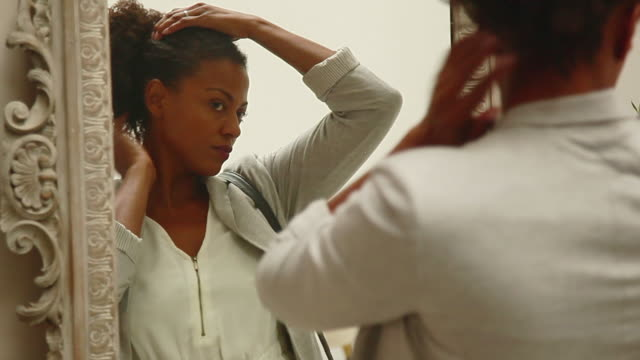 woman fixing hair in mirror - hair care stock videos & royalty-free footage