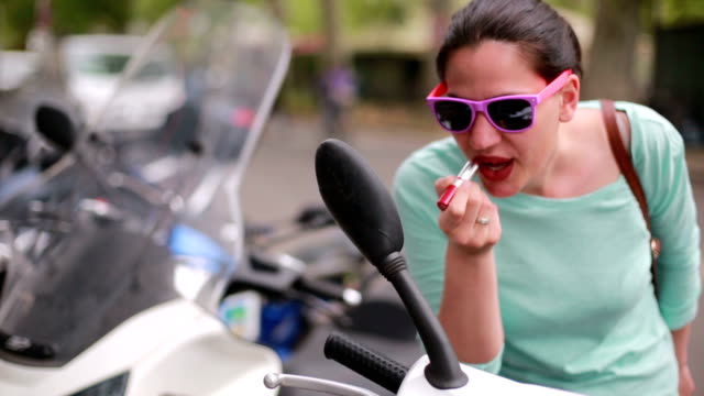 woman fixing her lipstick on rearview mirror - moped stock videos and b-roll footage