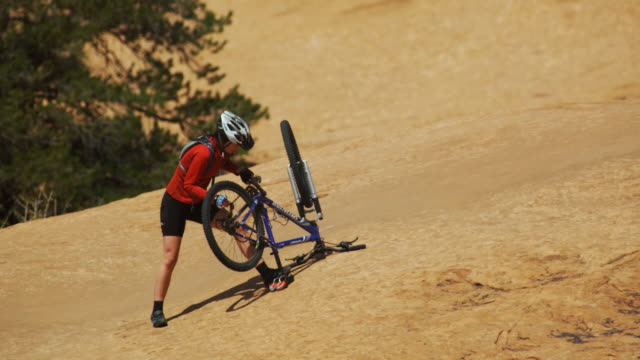 woman fixing her mountain bike - beschädigt stock-videos und b-roll-filmmaterial