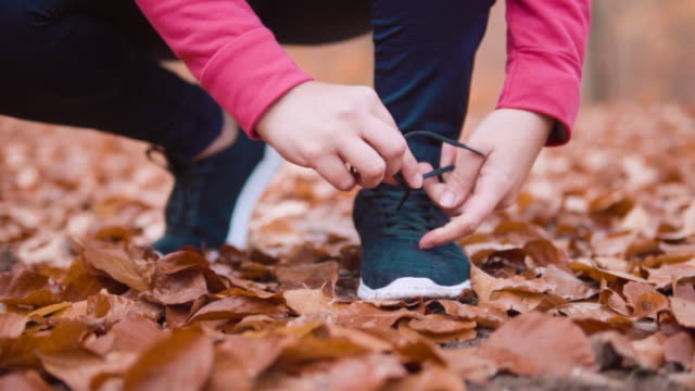 woman fixing her shoelaces before jogging. - shoelace stock videos and b-roll footage
