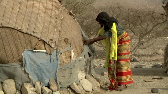 vídeos de stock e filmes b-roll de woman fixing straw on hut - pobreza