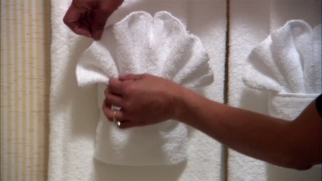 cu, pan, woman fixing towel arrangement in hotel bathroom, close-up of hands - handtuch stock-videos und b-roll-filmmaterial