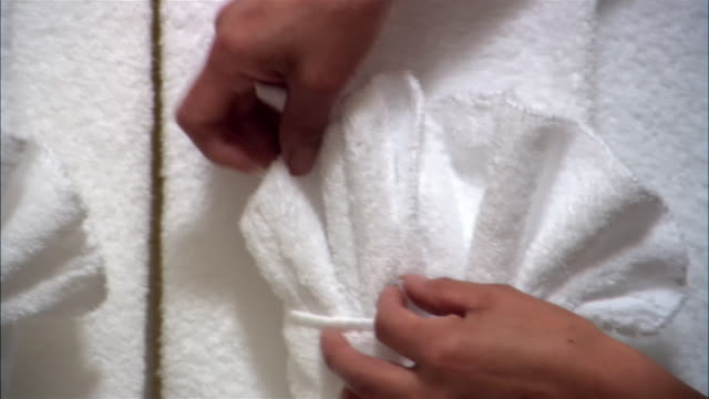 cu, woman fixing towel arrangement in hotel bathroom, close-up of hands - handduk bildbanksvideor och videomaterial från bakom kulisserna