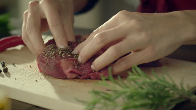 woman flavouring a piece of meat - meat stock videos & royalty-free footage