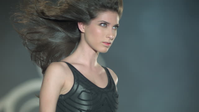 Woman flicks her hair and walks in forward motion wearing a black dress.
