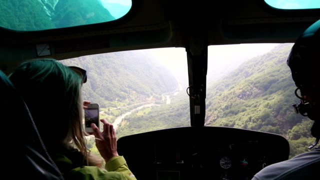 vídeos de stock e filmes b-roll de woman flies in helicopter alongside pilot, takes pictures - helicóptero