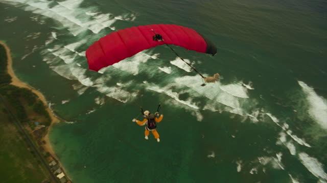 vídeos de stock e filmes b-roll de woman flies red parachute over the ocean - risco