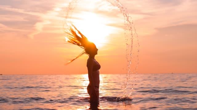 frau flippt ihr langes nasses haar zurück, während sie im meerwasser steht - schöne natur stock-videos und b-roll-filmmaterial