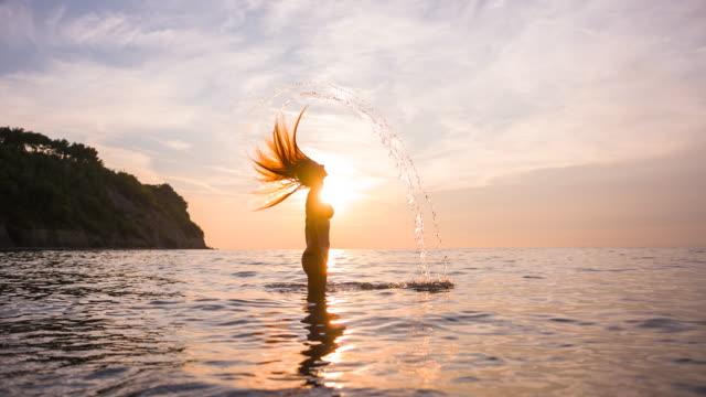 vidéos et rushes de femme, renversant ses cheveux en arrière en se tenant debout dans l'eau au coucher du soleil - cheveux mouillés