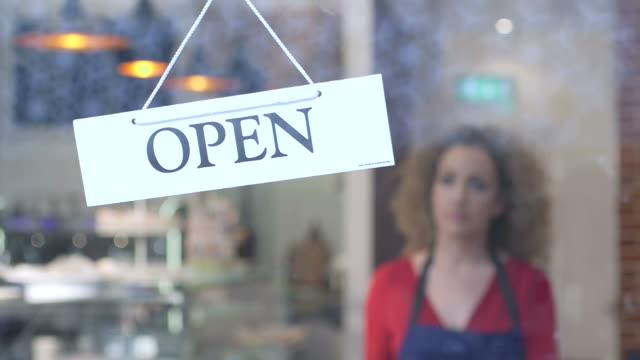 woman flipping over open sign - closed sign stock videos and b-roll footage