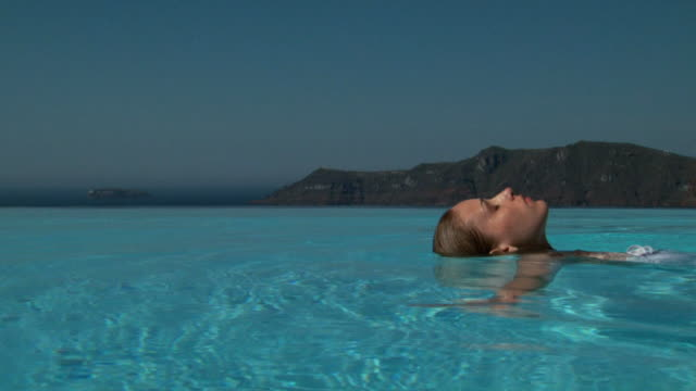 a woman floating across an infinity pool - see other clips from this shoot 1144 stock videos & royalty-free footage