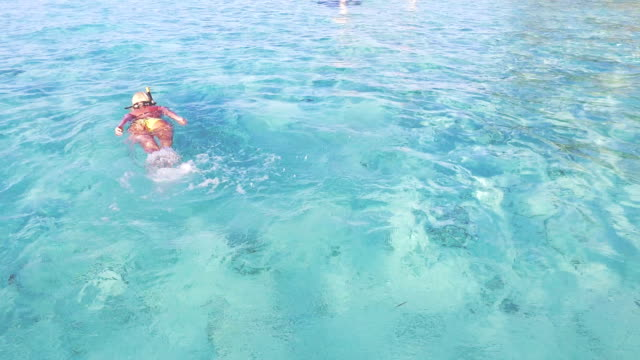 Woman floating and snorkeling in crystal clear water, Maldives