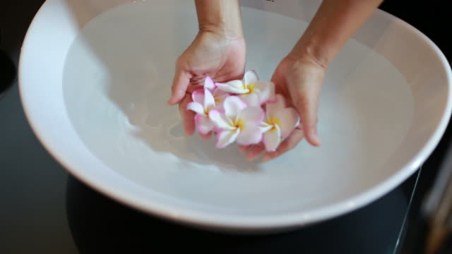 woman floating flower on washbasin - reflexology stock videos and b-roll footage