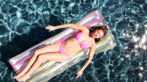 woman floating in swimming pool - sunbathing stock videos & royalty-free footage