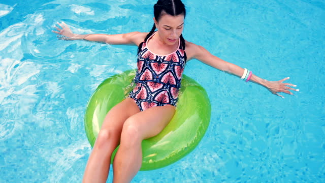 woman floating in swimming pool - inflatable raft stock videos and b-roll footage