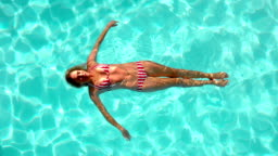 Woman floating in the swimming pool in cinemagraph
