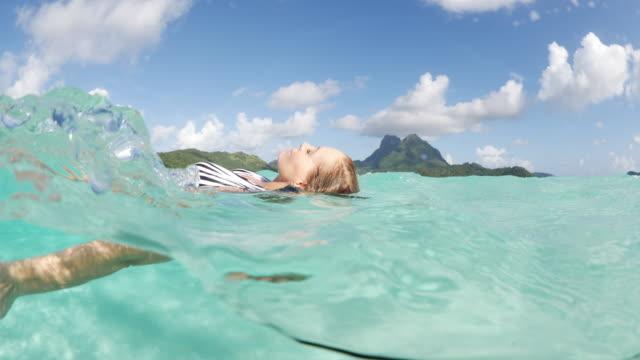 woman floating on back in ocean in tahiti / bora bora, french polynesia - bora bora stock videos and b-roll footage